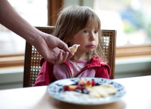 A picky eater refuses food at the dinner table.